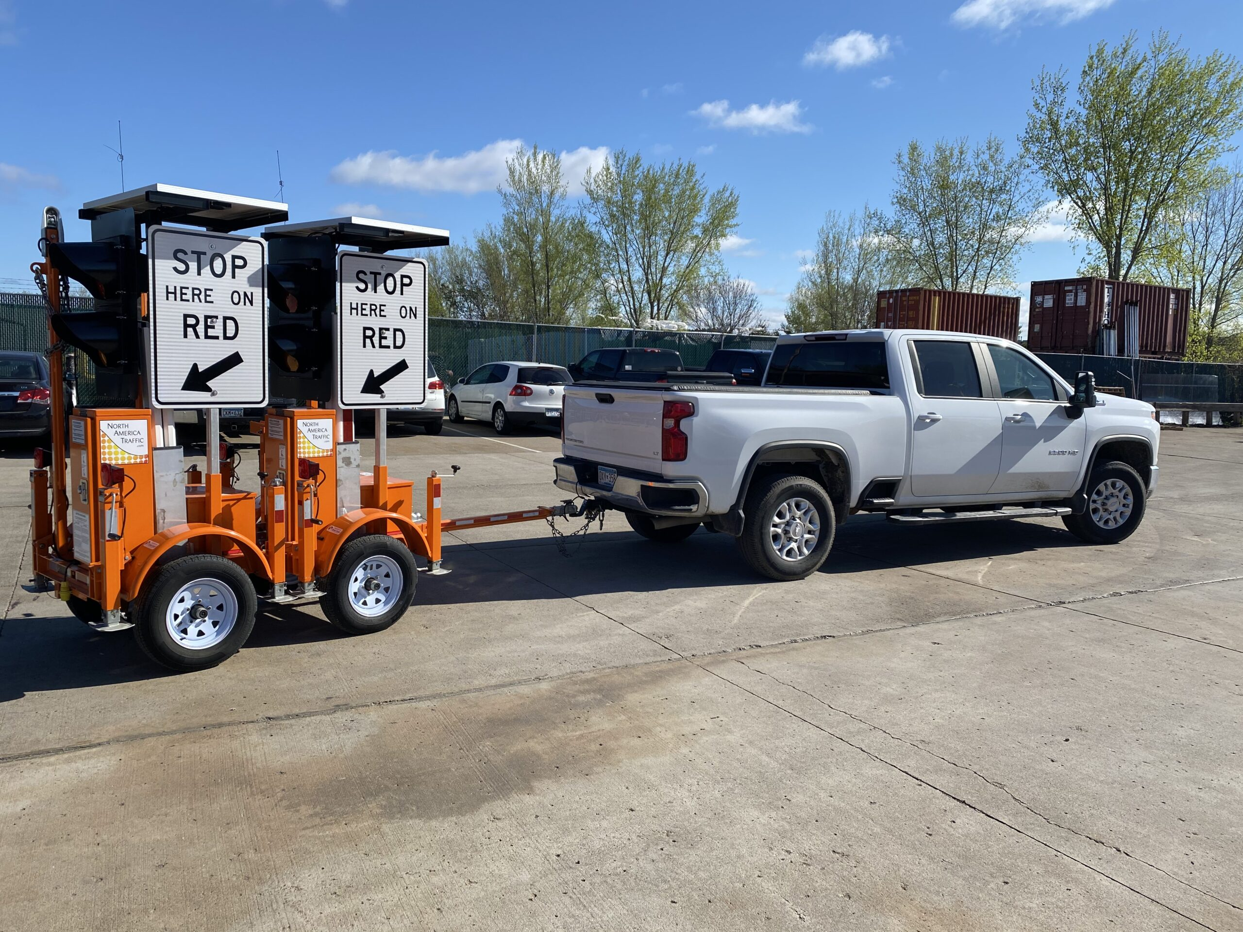 Two automated flagger devices being pulled by a white pickup truck